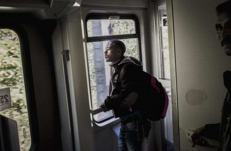 Due migranti eritrei stanno in attesa dentro al treno per Monaco di Baviera . 9800  Eritrei sono arrivati in Italia nel 2013