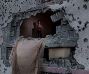 Gaza, Donia Ashraf Odwan, 6 anni, affacciata fra i ruderi della sua abitazione a Beith Hanoun Gaza